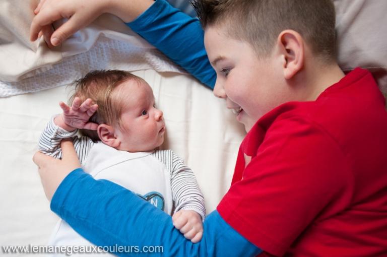 Séance photo nouveau-né à la maison - complicité avec le grand frère - photographe bébé nord pas de calais
