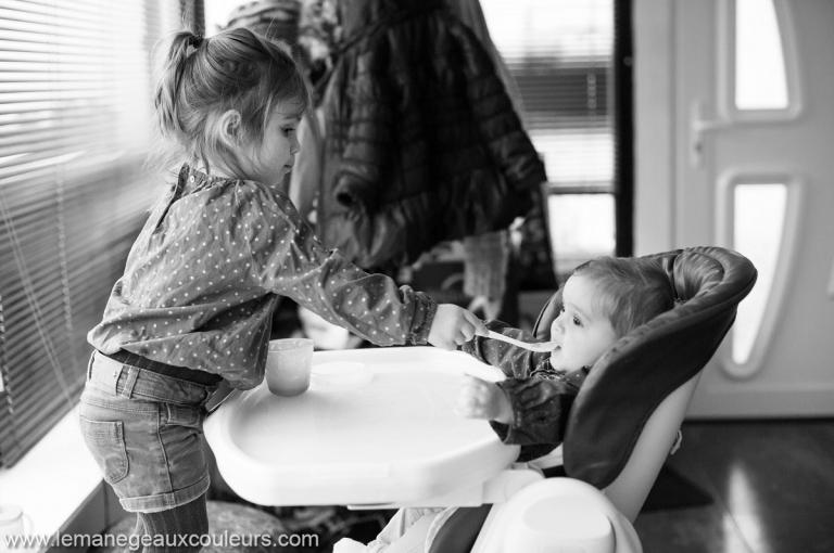 Séance photo bébé en famille photographier le quotidien commence par le repas donné par la grande soeur