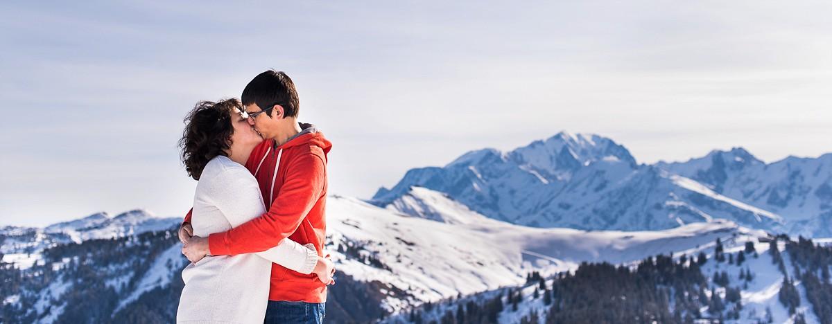 Séance photo de couple à la montagne dans la neige vue sur le mont blanc