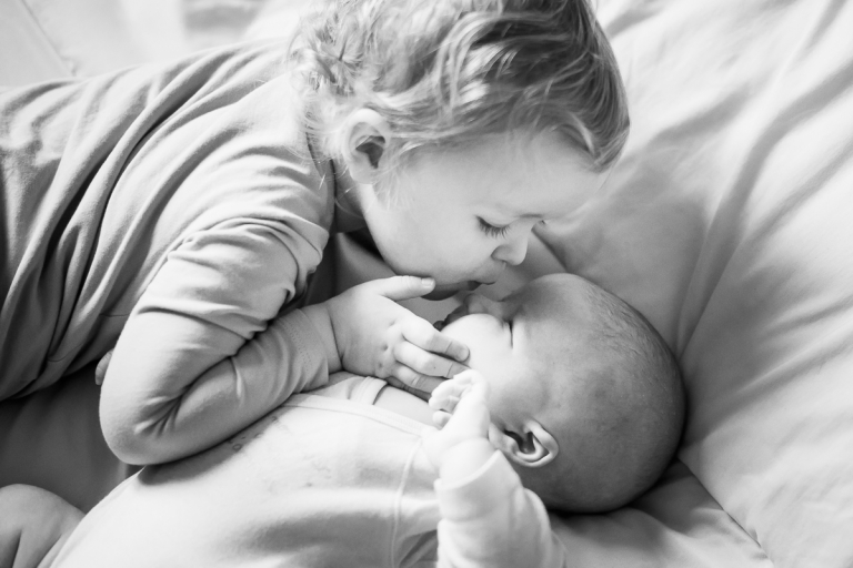 grande soeur faisant un bisou sur le nez de son petit frère photographe bébé Lille